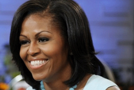 MICHELLE OBAMA STRAPPA IL CARTELLO